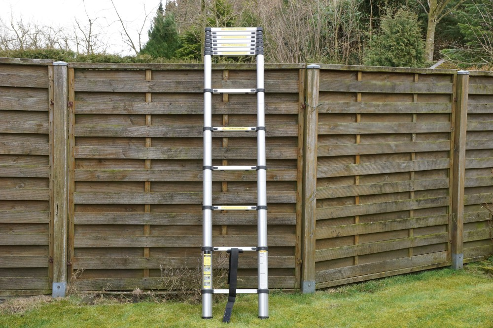 Telescopic ladder half-pushed against the garden fence